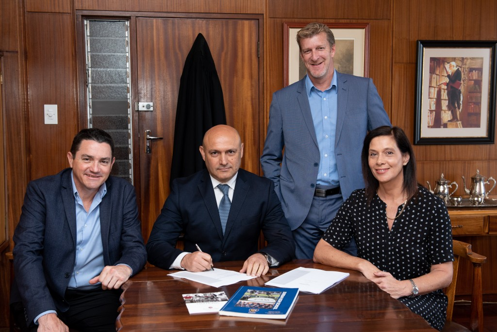 Craig Duff (left) and Odette Francesconi (right), the innovators and founders of NewBridge Institute (additionally the founders of Varsity College in 1991), pictured with DHS Head Master, Mr A D Pinheiro (seated middle) signing the lease for NewBridge Institute, Musgrave campus, located on the corner of St Thomas and Stephen Dlamini (Essenwood) Roadd, together with Roger Collins (standing), NewBridge Musgrave campus principal